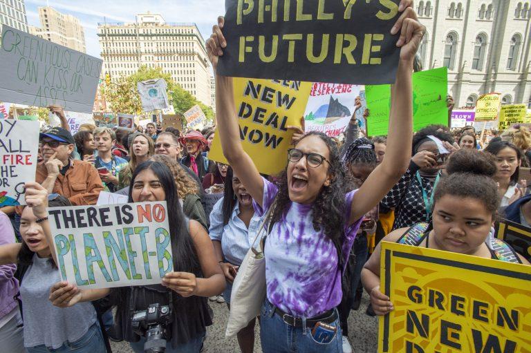 Masterman High School seniors Iman Acharya and Alina Kilcullen cheer for speakers at Philadelphia's climate strike on Sept. 20, 2019. (Jonathan Wilson for WHYY)