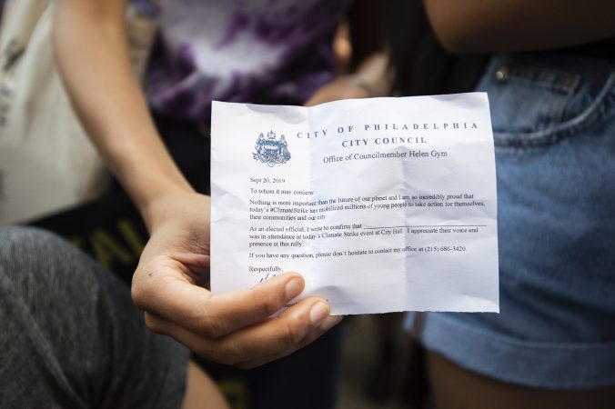 A student holds an school absentee excuse notice from Councilmember Helen Gym. (Jonathan Wilson for WHYY)