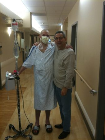 David with his Dad in the hospital. Courtesy of David Fajgenbaum