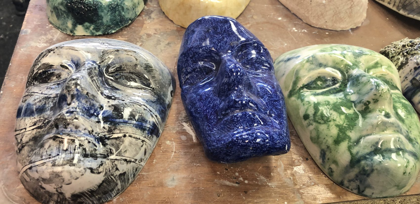Ceramic faces fill a table in the sculpting studio. (Cris Barrish/WHYY)