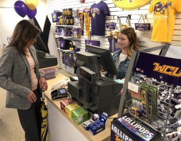 Monica Zimmerman, executive director of West Chester University's Entrepreneurial Leadership Center, purchases a travel mug from The Ram Shop at the edge of campus. WCU student Madeline Berger rings up the transaction. (P. Kenneth Burns/WHYY)
