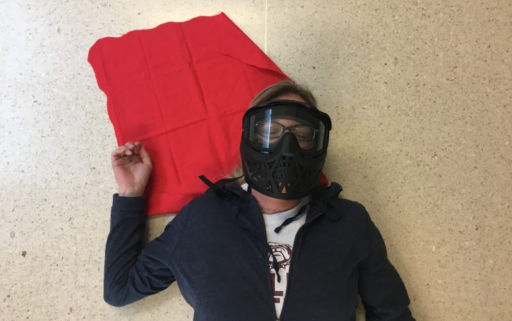 Angie lies on the ground, playing dead during a FASTER school shooting simulation. (Jen Kinney for Keystone Crossroads)