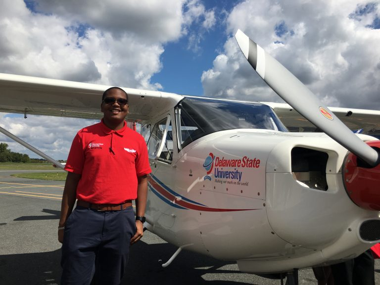 Sophomore Christian Black stands next to a new Vulcanair plane that he'll be training on at Delaware State University. (Mark Eichmann/WHYY)