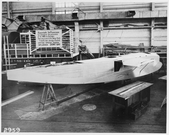 Hull of an experimental F6L flying boat under construction at the Naval Aircraft Factory, Philadelphia Naval Shipyard, with influenza precaution sign in background, October 19, 1918. (U.S. Naval History and Heritage Command Photograph, Catalog # NH 41731, Archives Branch, Naval History and Heritage Command, Washington, D.C.)