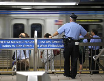 A transit police officer keeps watch on the Market-Frankford line. (Emma Lee/WHYY)