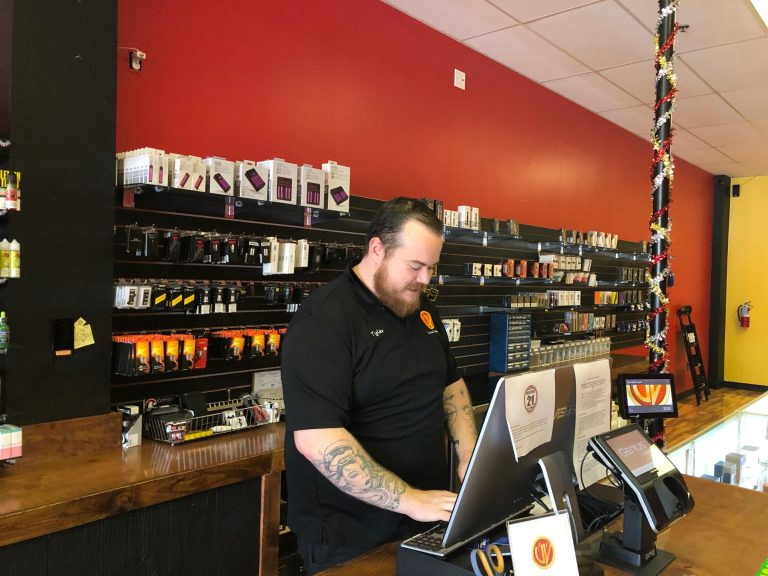 Tyler Wilson, assistant manager at Unreal Vapors near Newport, Del., rings up an order for a lemonade-flavored e-cigarette fluid. (Cris Barrish/WHYY)