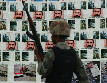 In this Dec. 16, 2005 photo, an Iraqi soldier guards at a checkpoint backdropped with posters, some are pictures of terror leader Abu Musab al-Zarqawi, in Baghdad, Iraq. (AP Photo/Hadi Mizban)