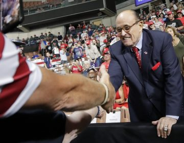Former New York City Mayor Rudy Giuliani shook hands with supporters as he arrived at President Trump's campaign rally on Aug. 15, 2019, in Manchester, N.H. (Elise Amendola/AP)