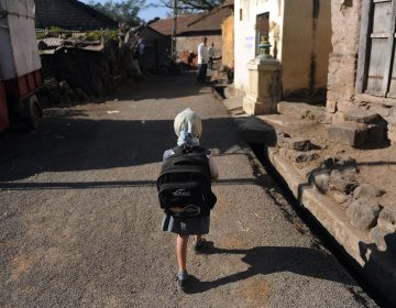A child leaves for school in a village in India. Last November, the Indian government announced new rules limiting the weight of school bags depending on a child's age. But the rules are not always enforced. (Punit Paranjpe /AFP/Getty Images)