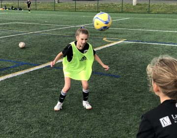 Eleven-year-old Ella Koehler, of Seattle United soccer club, heads the ball at a practice on the University of Washington campus. It's the first year she and her teammates of the same age can use the technique. A 2015 rule by the U.S. Soccer Federation banned heading for kids ages 10 years old and younger. (Tom Goldman/NPR)