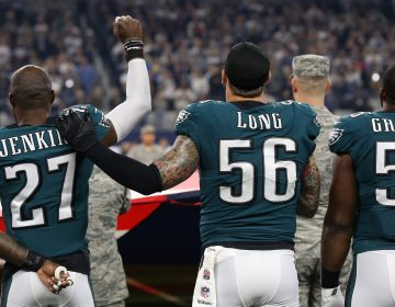 Eagles safety Malcolm Jenkins (left) raises a fist during the national anthem in 2017 as teammate Chris Long (right) places a hand on his shoulder in solidarity MATTHEW EMMONS / USA TODAY SPORTS