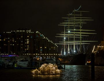 Stephen Talasnik's Endurance sits illuminated in the Delaware River boat basin ready for the opening of the FLOW exhibition. FLOW is a sculpture exhibit on the Delaware River in partnership with Philadelphia Sculptors and the Independence Seaport Museum. (Emily Cohen for WHYY)