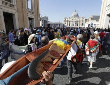 Saturday, Oct. 19, 2019, members of Amazon indigenous populations walk during a Via Crucis (Way of the Cross) procession from St. Angelo Castle to the Vatican. In foreground is a wooden statue portraying a naked pregnant woman. (Andrew Medichini/AP Photo)