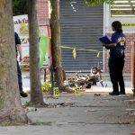 Police investigate a 2018 drive-by shooting in Germantown. The City's Controller has found that a homicide reduces the values of a nearby homes. (Emma Lee/WHYY)