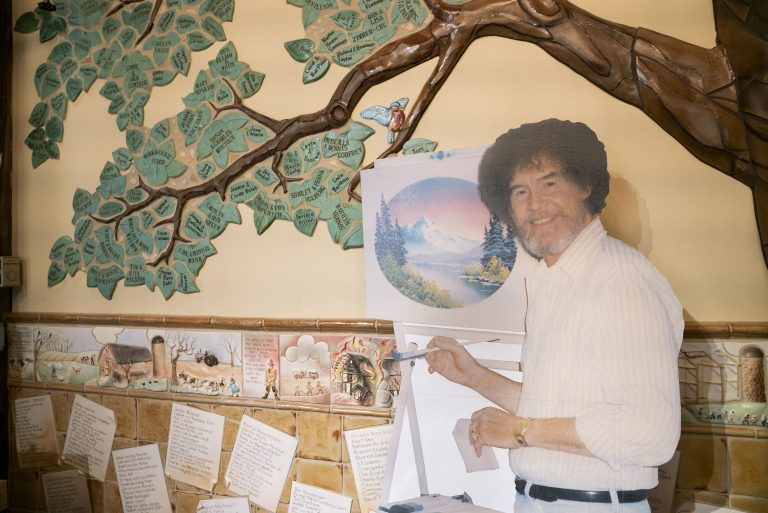 A life size cut out of Bob Ross stands up against the wall where the historical tree of the Franklin Park Arts Center is painted. Bob Ross Inc. is located in Herndon, Va., which is only 27 miles from the exhibit. According to managing director, Elizabeth Bracey, the exhibit was intentionally kept close to headquarters. (Mhari Shaw/NPR)