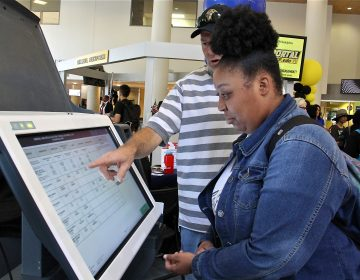 Community College of Philadelphia student Hanna Archibald, 20, learns how to use a new voting machine from Matthew McKeon of the City Commissioners Office. (Emma Lee/WHYY)