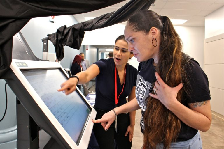 Diane Duffin learns how to use a voting machine with the help of Michelle Montalvo of the City Commissioners Office. Duffin registered to vote for the first time after learning that a conviction did not prevent her from voting in Pennsylvania. (Emma Lee/WHYY)