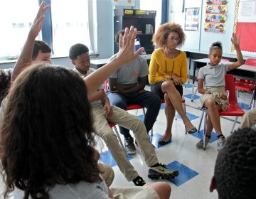 Students at Memphis Street Academy raise their hands during a student wellness meeting. (Emma Lee/WHYY)