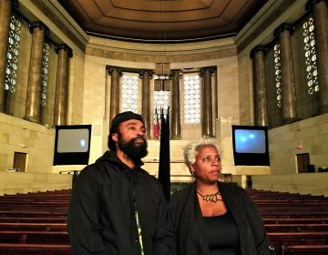 Bradford Young and Elissa Blount Moorhead stand in the Girard College chapel with their video installation, 'Back and Song.' (Peter Crimmins/WHYY)