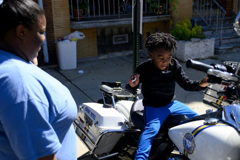 Octavia Abney watches her son Dylan, 4, sit on a Philadelphia Police Department motorbike during the Love Peace and Soul Fest block party on Sunday October 5, 2019 at the site of the August Police shooting and stand off in the Nicetown-Tioga section of Philadelphia. (Bastiaan Slabbers for WHYY)