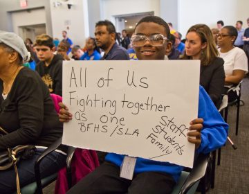 Maurice Boston, a freshman at Ben Franklin H.S., shows his support at a packed meeting discussing the closures of Ben Franklin and Science Leadership Academy high schools because of asbestos remediation at the school district building Monday morning. (Kimberly Paynter/WHYY)