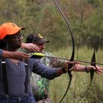 Markeeta Holmes hones her skills with a recurve bow with the help of mentor A.J. Garcia. Holmes participated in the mentored deer hunt at John Heinz National Wildlife Refuge at Tinicum. (Emma Lee/WHYY)