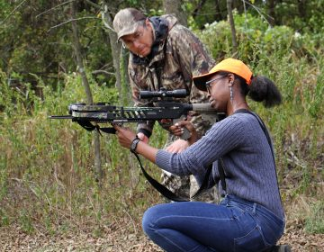 Markeeta Holmes, 25, of North Philadelphia, takes target practice with a mentor at the John Heinz National Wildlife Refuge at Tinicum. (Emma Lee/WHYY)