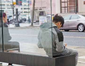 A commuter listens to music while they wait for a SEPTA bus. (Kimberly Paynter/WHYY)