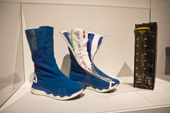 Space boots designed by Reebok and a cubesat, a small device designed to collect data in space, at the Designs for Different Futures exhibit at the Philadelphia Art Museum. (Kimberly Paynter/WHYY)