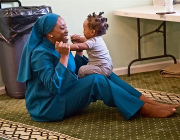 Tahirah Austin, who has sickle-cell disease, plays with Kinza, the son of a friend who also has the disease. (Kimberly Paynter/WHYY)