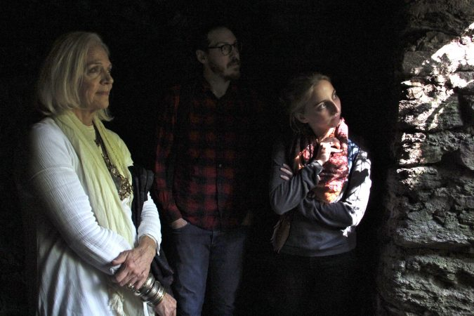 Kris Soffa, Shai Ben-Yaacov and Kelsey Hanson look out on the woods of the Wissahickon from the Cave of Kelpius. It is believed that Kelpius and his followers used the cave to store books and scientific equipment. (Emma Lee/WHYY