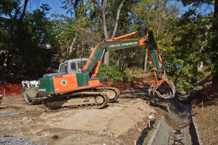 An excavator removes concrete pipe as part of a plan to restore a waterway at Conklin Recreation Center. (Kimberly Paynter/WHYY)