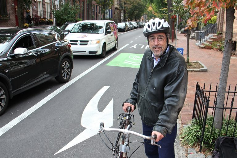 Larry Spector, president of the Society Hill Civic Association, hops off his bike at 5th and Pine streets. (Emma Lee/WHYY)