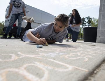 Sophomore Fatima Saldana, 16, works on her message as National Children's Mental Health Awareness Day is celebrated with students participating in Messages of Hope, which had them writing positive messages in chalk by the school entrance Thursday, May 10, 2018, at Oakcrest High School in Mays Landing, N.J. (Matthew Strabuk/The Press of Atlantic City via AP)