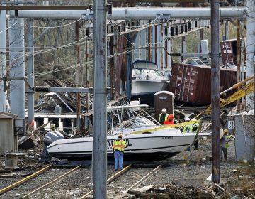 In this Oct. 31, 2012 file photo, workers try to clear boats and debris from the New Jersey Transit's Morgan draw bridge after surge from Sandy pushed boats and cargo containers onto the train tracks. (Mel Evans/AP Photo, File)