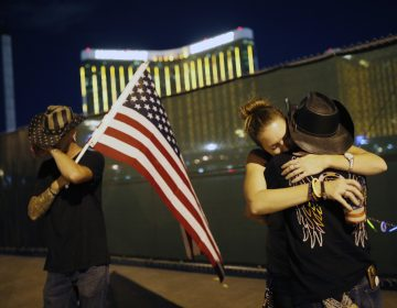Megan Murphy, right in hat, embraces Cara Knoedler as Kenneth Wright wipes his eyes on the first anniversary of the mass shooting in Las Vegas. Behind them is the site of the shooting. (John Locher/AP Photo)