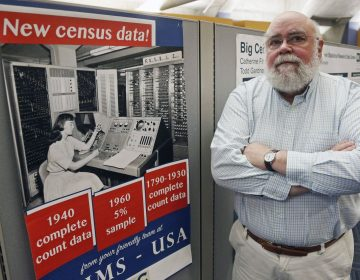 Steven Ruggles, director of the Institute for Social Research and Data Innovation at the University of Minnesota, poses next to a Census Bureau poster. (Jim Mone/AP Photo)