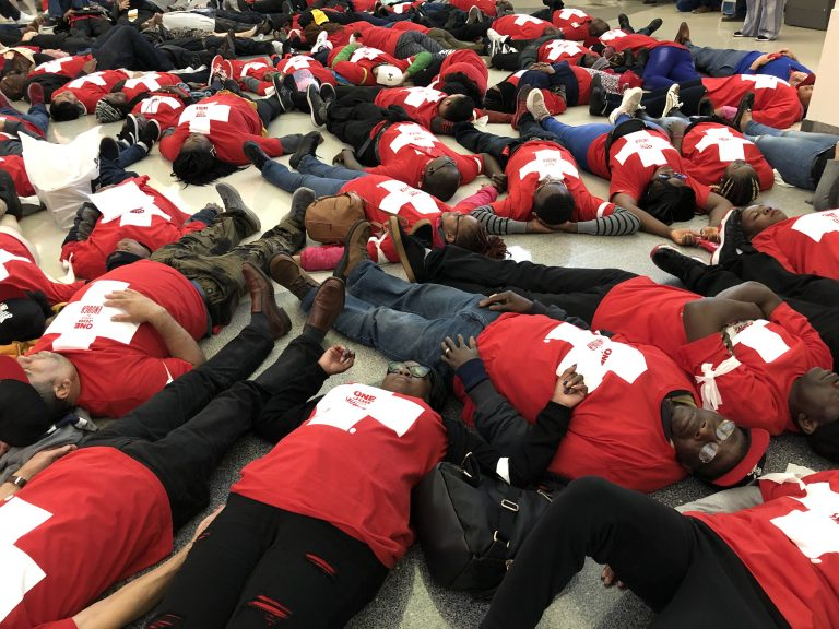 Food prep workers die-in at the Philadelphia airport on Wednesday night to demonstrate the life and death stakes of lacking affordable healthcare. (Nina Feldman/WHYY)