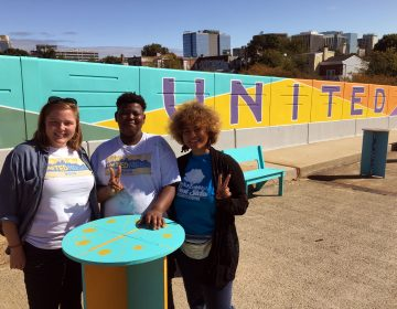 West Side Grows Together's Sarah Lester, volunteer Brenden Cephas and United Neighbors organizer Vanity Constance stand in front of a mural on the Seventh Street bridge over I-95. (Mark Eichmann/WHYY)
