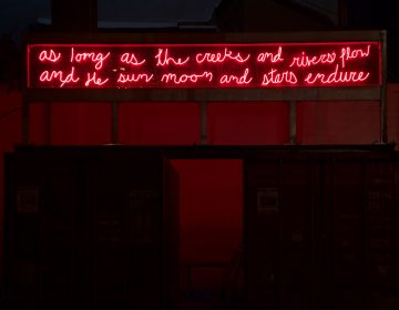 """'In Perpetuity' by Duane Linklater: """"In Perpetuity"""" uses bright red neon to spell out a translated quote from Chief Tamanend who negotiated the Treaty of Shackamaxon. 'As long as the creeks and rivers flow and the sun, moon and stars endure,' the neon sculpture says. (Kimberly Paynter/WHYY)"""