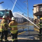 Firefighters attacking the flames of a fire in an auto shop at 59th and Irving streets in West Philly. (Kimberly Paynter/WHYY)