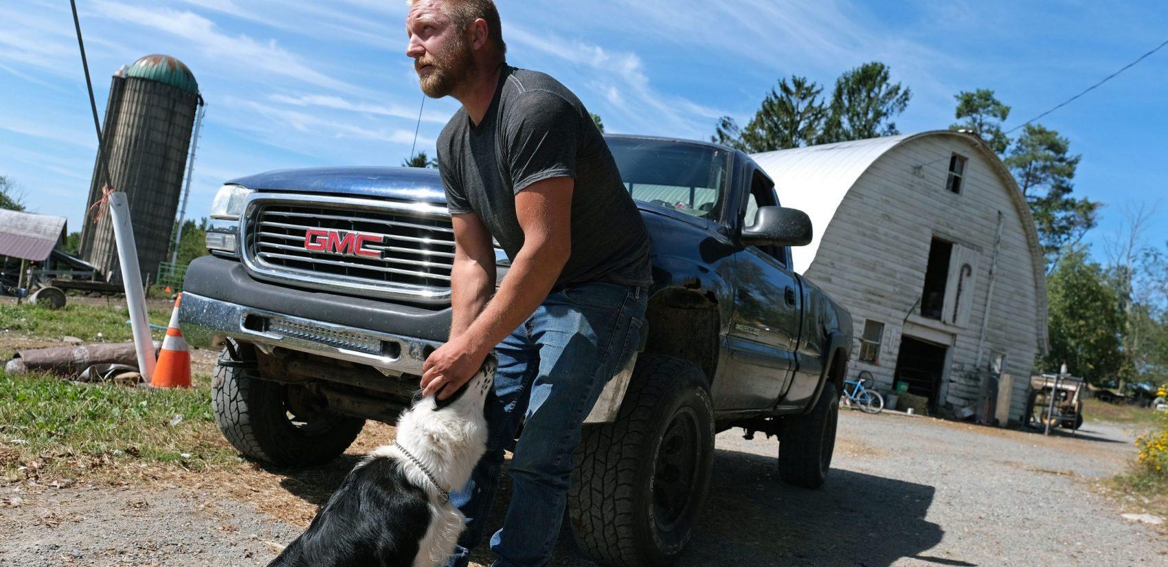 Grain farmer Jesse Poliskiewicz pets a dog while visiting his father's farm Sept. 20, 2019, in Upper Mount Bethel Township, Pennsylvania. (Matt Smith for Keystone Crossroads)