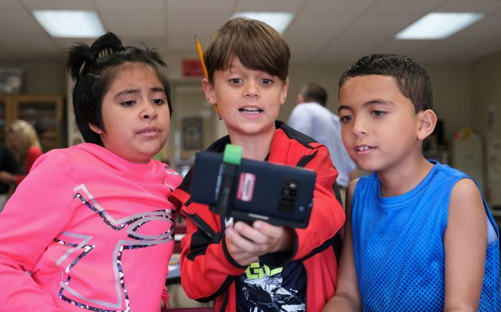 Rocio Vasquez, left, 8, Patrick Krick, center, 9, and Eliel Ramos, right, 8, work with a tornado simulation augmented reality program on a smartphone Sept. 26, 2019, at Whitfield Elementary School in Spring Township, Pennsylvania. (Matt Smith for Keystone Crossroads)