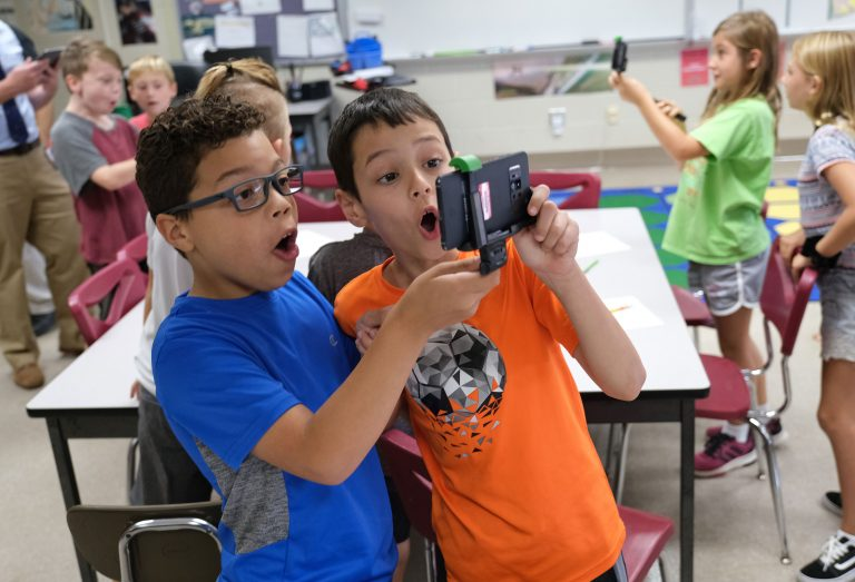 Dante Guzman, left, 8, and Emre Tokuc, right, 8, work with a tornado simulation augmented reality program on a smartphone Sept. 26, 2019, at Whitfield Elementary School in Spring Township, Pennsylvania.  (Matt Smith for Keystone Crossroads)