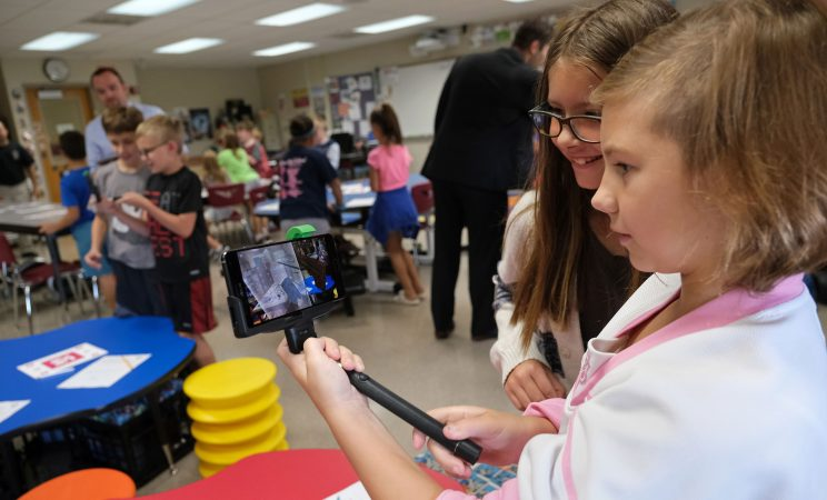 Aalyah Bleyer, left, 9, and Isabella Rothermel, right, 8, work with a tornado simulation augmented reality program on a smartphone Sept. 26, 2019, at Whitfield Elementary School in Spring Township, Pennsylvania. (Matt Smith for Keystone Crossroads)