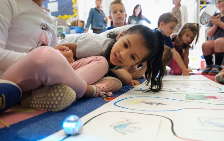 Franmely Mundaray-De La Cruz, 6, leans over to watch an Ozobot move as she uses it to tell a story alongside fellow students Sept. 26, 2019, at Mifflin Park Elementary School in Cumru Township, Pennsylvania. (Matt Smith for Keystone Crossroads)