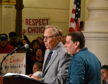 Philadelphia-based attorney Theodore Schwartz, at left, talks at a rally for people with intellectual disabilities. At right is his son, Scott (Brett Sholtis/Transforming Health)