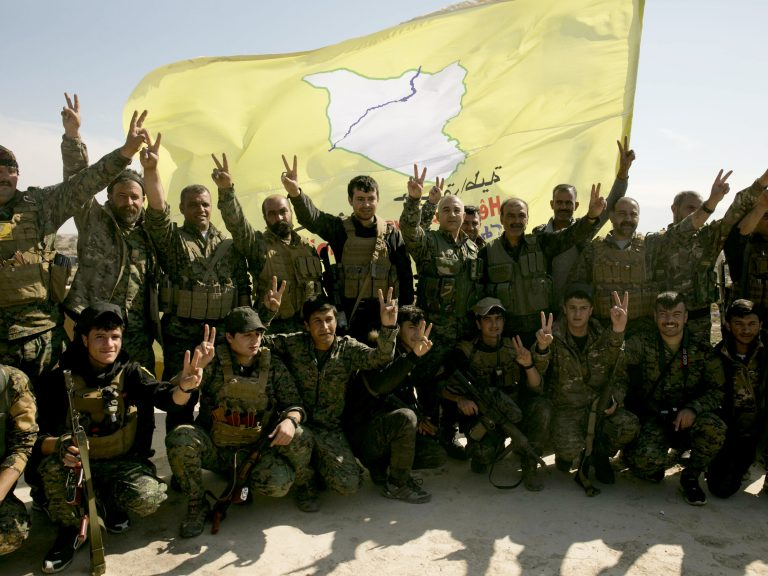 U.S.-backed Syrian Democratic Forces (SDF) fighters pose for a photo in Baghouz, Syria, after the SDF declared the area free of Islamic State militants, in March. (Maya Alleruzzo/AP)