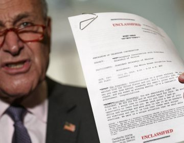 Senator Chuck Schumer holds up the White House transcript of a call between President Donald Trump and the president of Ukraine. (Jacquelyn Martin/AP Photo)