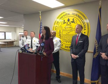 Delaware County District Attorney Katayoun Copeland (center) announces charges against 22 people, all alleged members of two Chester drug gangs. (Avi Wolfman-Arent/WHYY)